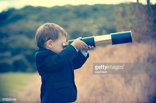 Kleiner Junge im business-Anzug mit Teleskop.