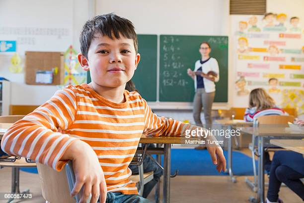young boy in a classroom facing the camera