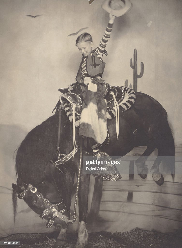 Young Boy in a Cowboy Costume Sitting on a Horse : Stock Photo