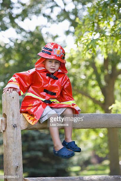 A young boy in a firefighter costume sitting on a fence