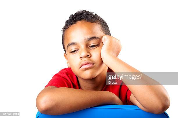 A young boy in a red shirt is bored and tired