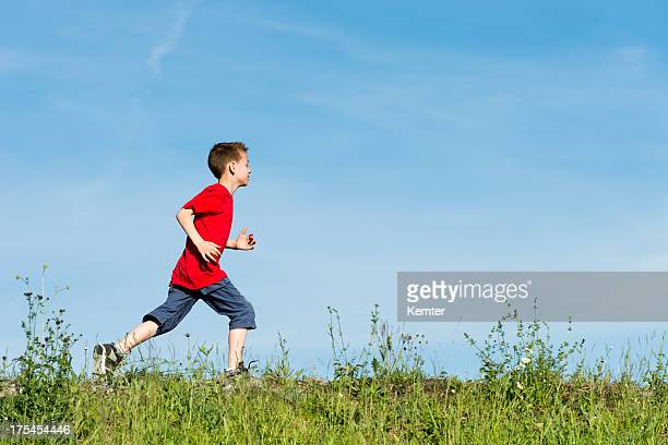 Young boy in a red t-shirt running on green grass