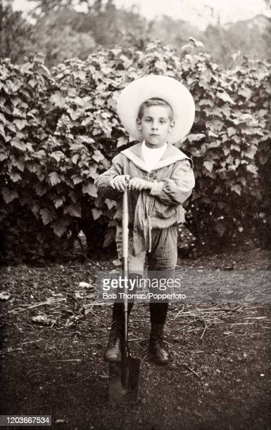 Young boy in a sailing cadet's outfit digging with a spade, circa June 1908.