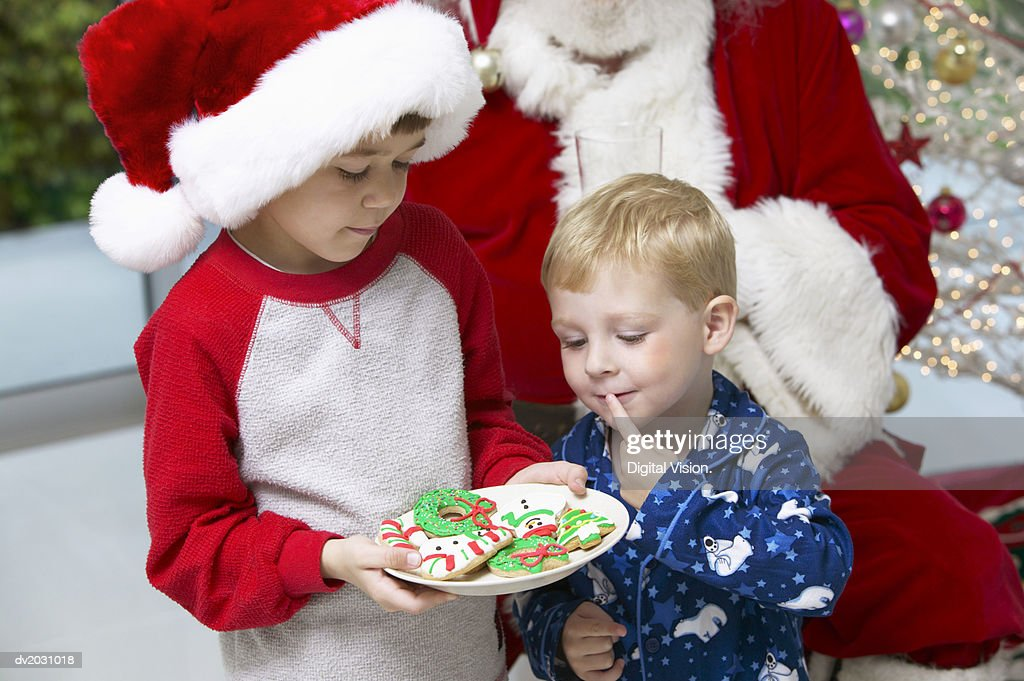 Young Boy in a Santa Hat Offers a Christmas Cookie to His Brother, Santa in the Background : Stock Photo