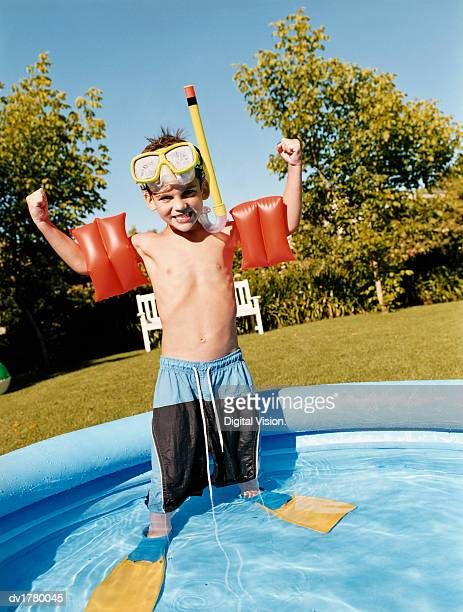 Young Boy in a Snorkel Stands Showing Off His Arm Bands in a Paddling Pool