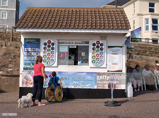 Young boy in a wheelchair at an ice cream kiosk Seaton Devon UK