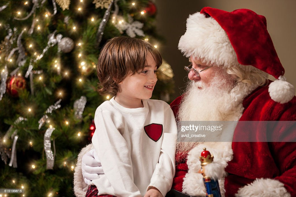 Young Boy in Awe Sits on Santa's Lap : Stock Photo