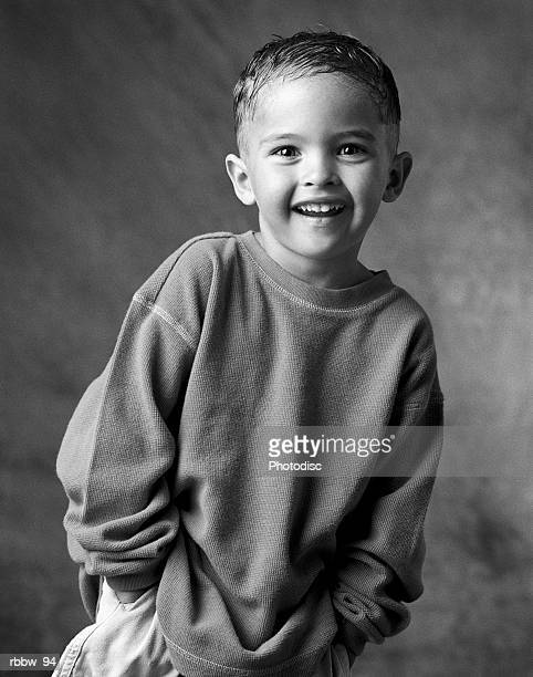 A young boy in baggy clothes smiles with his hands in his pockets