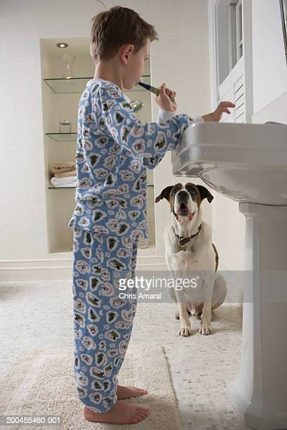 Young boy (6-8) in bathroom brushing teeth looking at dog