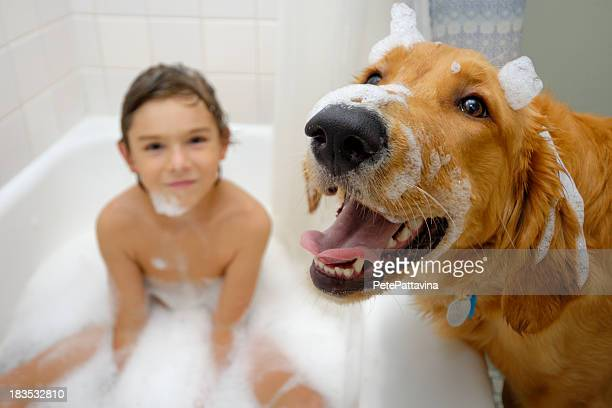 Young boy in bathtub and dog foreground
