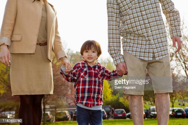 a young boy in between his parents, holding hands - femme entre deux hommes photos et images de collection