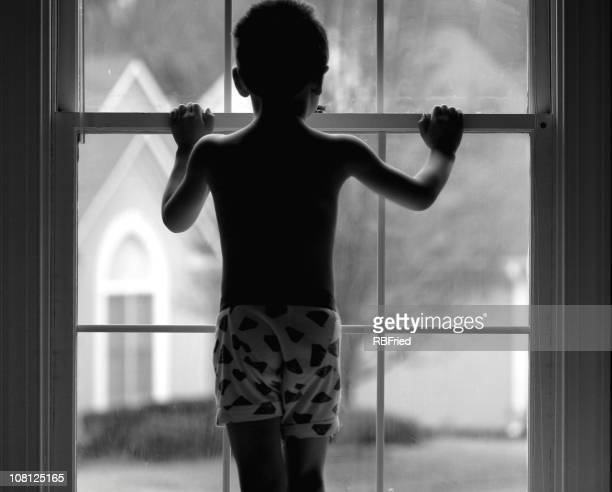 Young boy in black and white photo gazing out of the window
