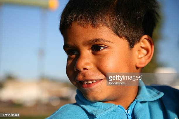 Young boy in blue sweater outside in sunshine