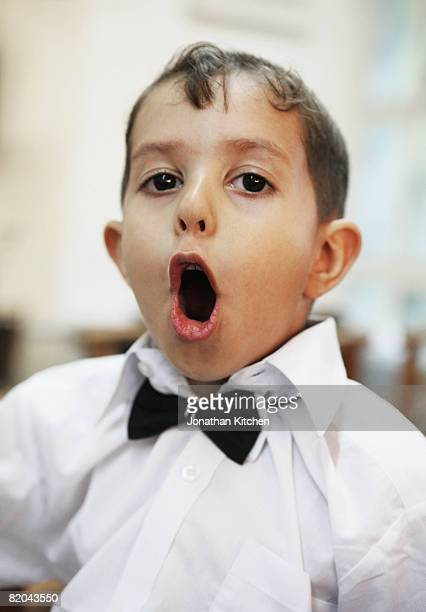 Young boy in bow tie singing