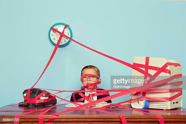 Young Boy in Business Office is Covered in Red Tape