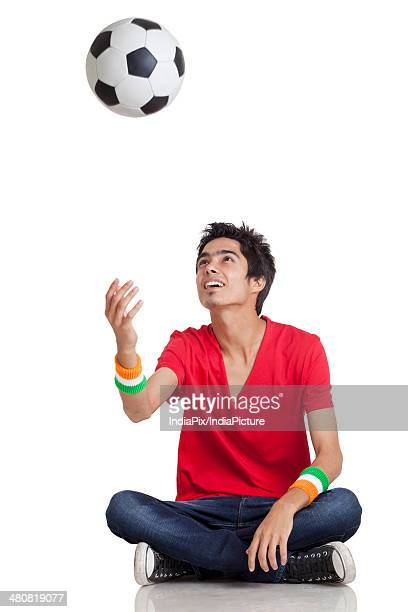 Young boy in casuals tossing soccer ball while sitting cross-legged over white background