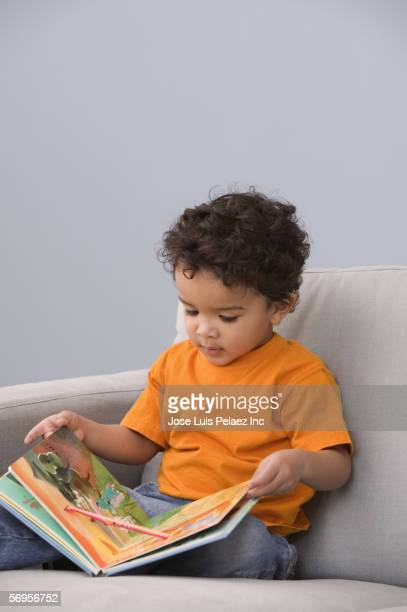 young boy in chair reading book - puerto rican ethnicity stock pictures, royalty-free photos & images