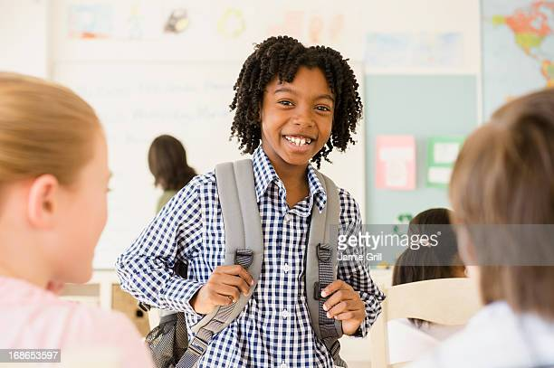 young boy in classroom, smiling - education stock pictures, royalty-free photos & images