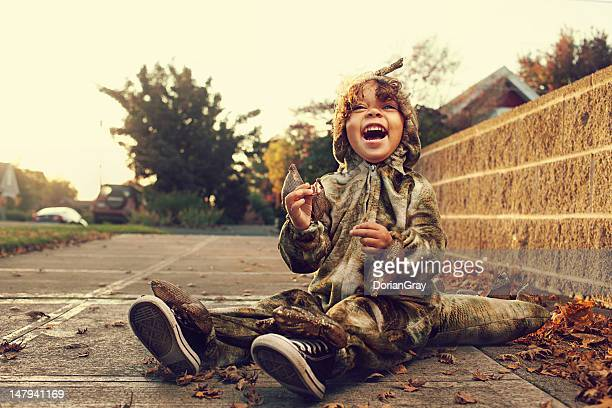 young boy in dinosaur costume during halloween - halloween kids stock photos and pictures