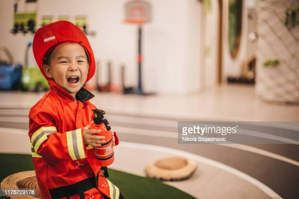 young boy in fireman costume - dressing up stock pictures, royalty-free photos & images