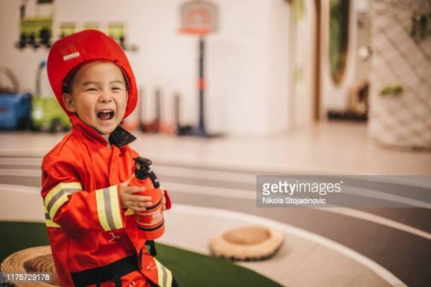 joven con traje de bombero - disfrazar fotografías e imágenes de stock