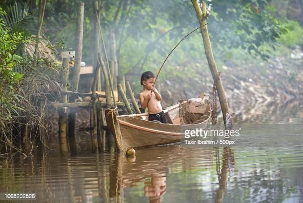 young boy in fishing boat - barco pesquero fotografías e imágenes de stock