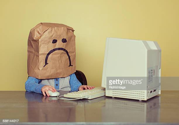 young boy in front of computer is cyber bullying victim - anti bullying symbols stock pictures, royalty-free photos & images