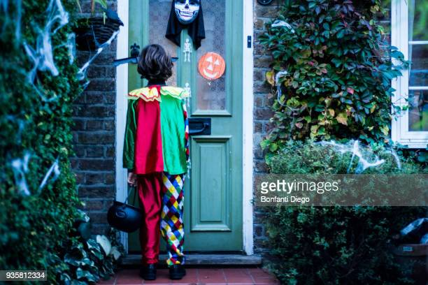 young boy in halloween costume, standing at door, trick or treating, rear view - naughty halloween stock photos and pictures