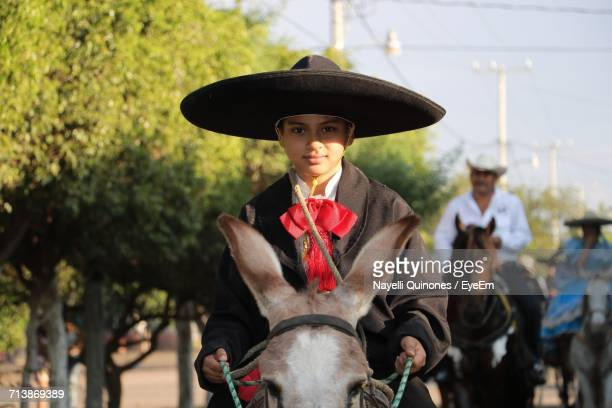 young boy in hat - mexican riding donkey stock photos and pictures