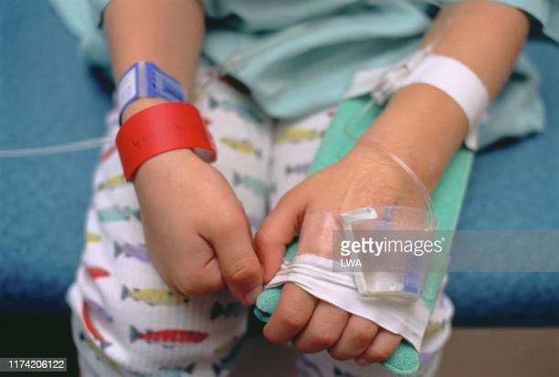 young boy in hospital bed showing intravenous lines in arm - canada stock pictures, royalty-free photos & images
