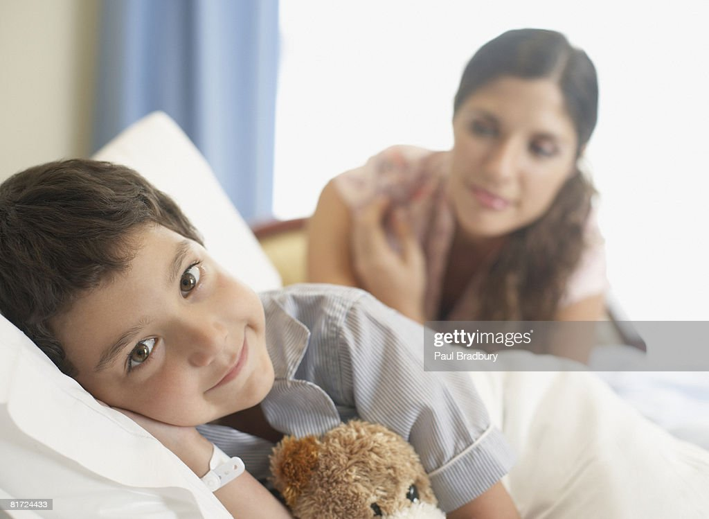Young boy in hospital bed smiling with woman looking over him : Stock Photo