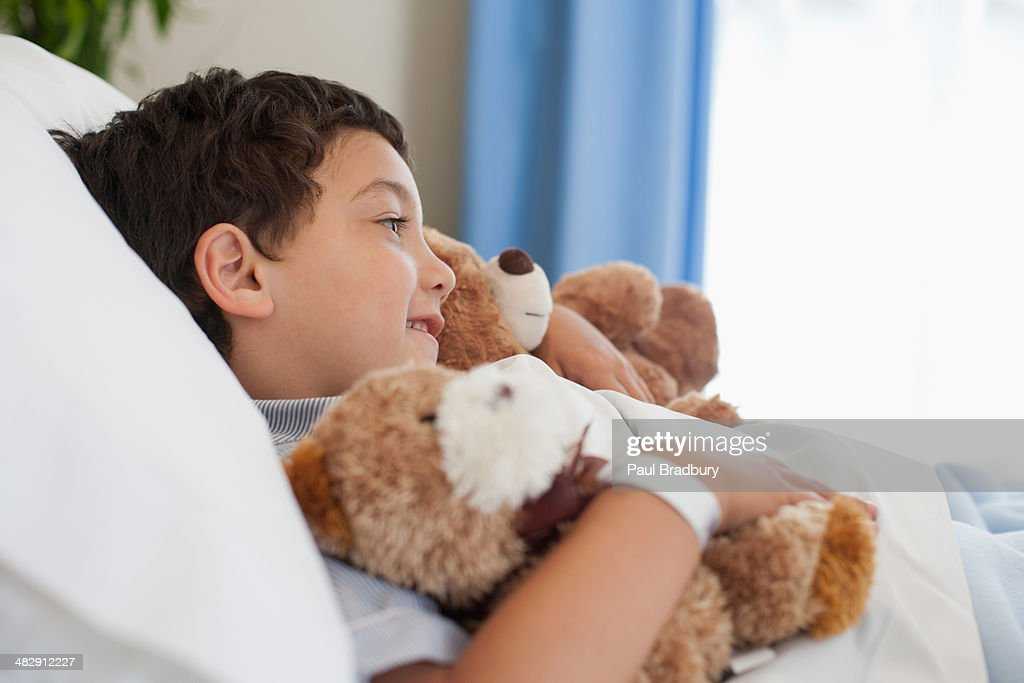 Young boy in hospital bed with teddy bears : Stock Photo