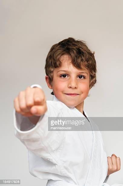 young boy in karate suit doing movement of a kata - judo stock photos and pictures