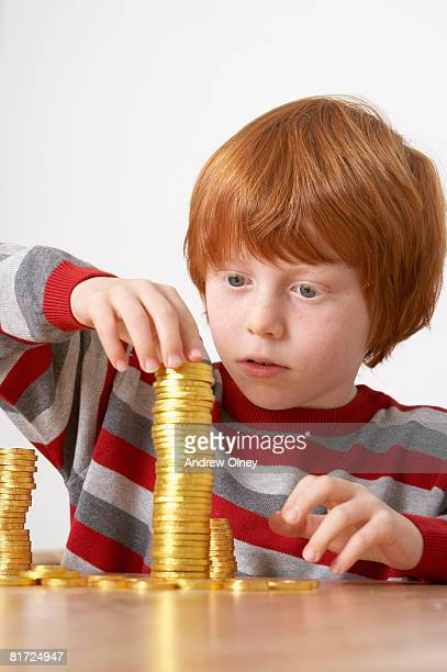 Young boy in kitchen piling up chocolate gold coins