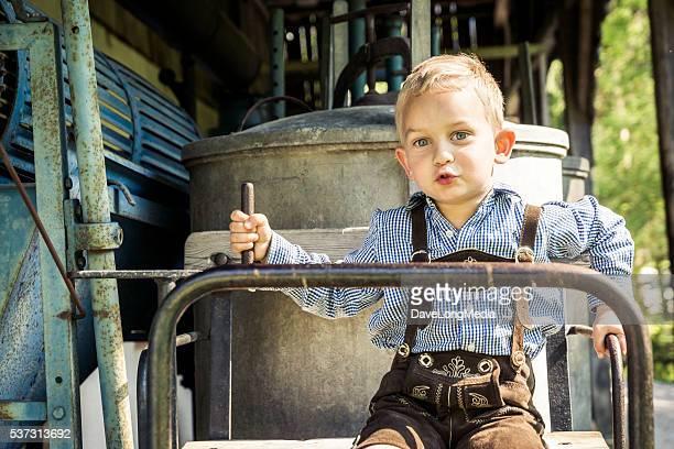Junger Mann in Lederhose-Trachtenmode spielen auf altes Dampfbad Wagon