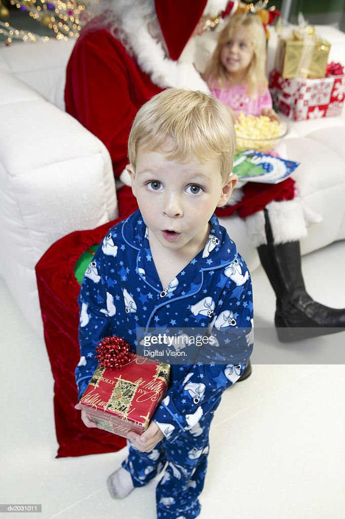 Young Boy in Pyjamas Excitedly Holds a Christmas Present, Father Christmas in the Background : Stock Photo