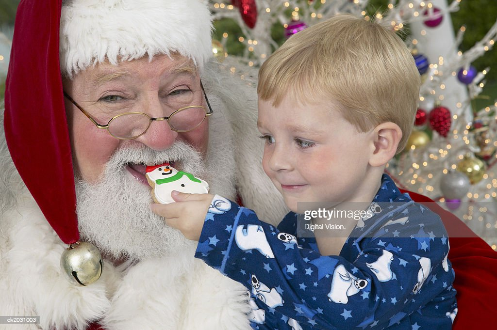 Young Boy in Pyjamas Feeds Father Christmas a Snowman Cookie : Stock Photo