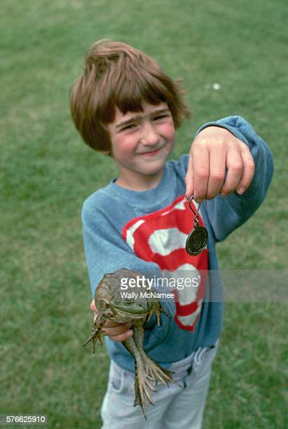 A young boy in Rhode Island displays his awardwinning jumping frog and the medal they won in a frog jumping contest which was part of a celebration...
