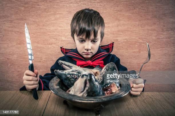 Junge im Matrosenanzug Contemplates Fischköpfe Unenthusiastically