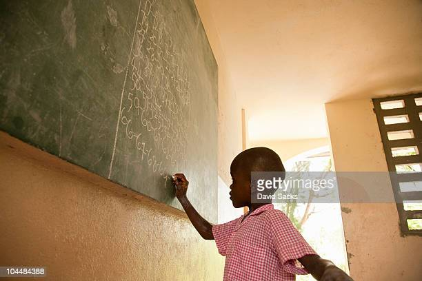 Young boy in school writing on chalkboard