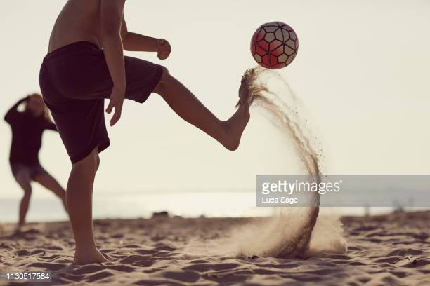 young boy in shorts kicks a football on the beach with sand flying in its wake - kicking stock pictures, royalty-free photos & images