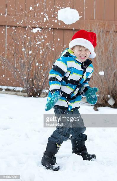 Jeune garçon dans la bataille de boules de neige