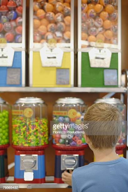Young boy in store using gumball machine