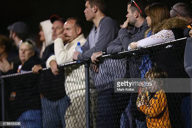 A young boy in the crowd watches on through the fence during the round 16 NRL match between the Wests Tigers and the Penrith Panthers at Leichhardt...