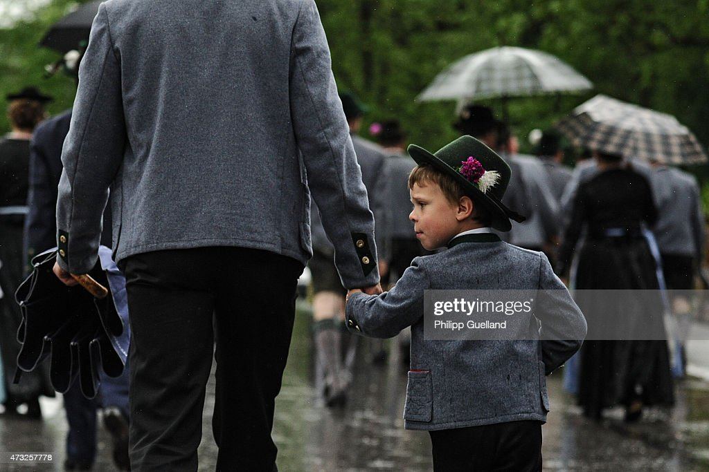 A young boy in traditional Bavarian folk dress holds his father's hand as he walks to attend the annual Ascension Mass (in German called Christi Himmelfahrt) at the open-air altar at Birkenstein on May 14, 2015 near Fischbachau, Germany. Several thousand pilgrims from 40 different folk group associations participated in the annual event to mark Jesus Christ's ascension to Heaven in a tradition going back centuries. Bavaria is predominantly Catholic.