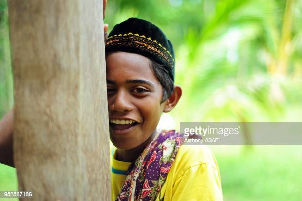 young boy in traditional dress smiling and hiding behind tree Banda Aceh Sumatra Indonesia