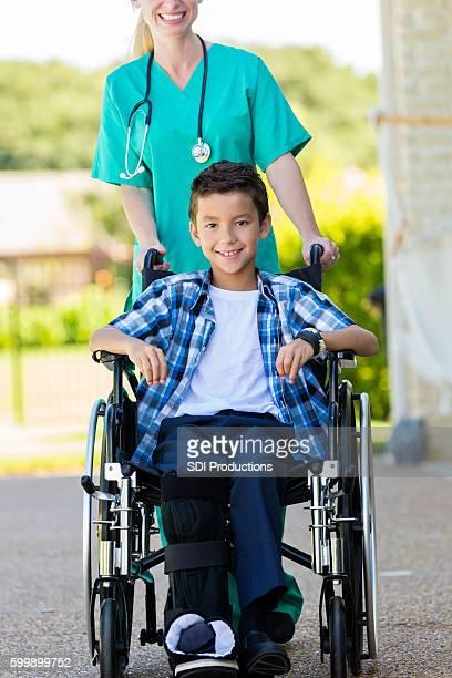 young boy in wheelchair being pushed by a nurse - pierna escayolada fotografías e imágenes de stock