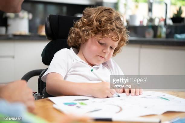 kleiner junge im rollstuhl, die zeichnung am esstisch - 6 7 jahre stock-fotos und bilder