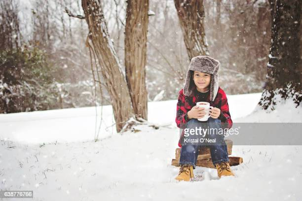 Young boy in woods sitting by tree in snow enjoying warm drink