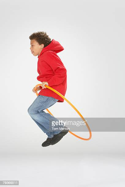 Young boy indoors jumping through a hula hoop